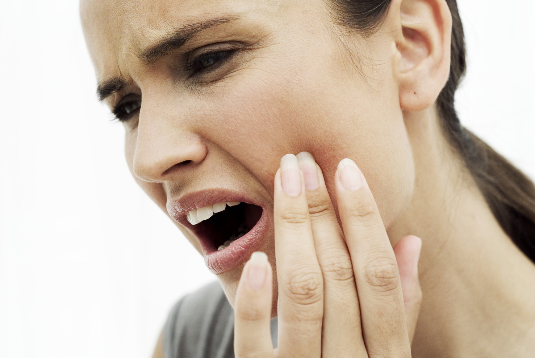 close-up of a young woman holding her cheek in pain